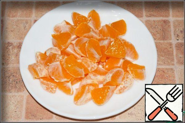Peel the tangerines and divide them into slices. Cut each slice in half, removing the seeds, if any.