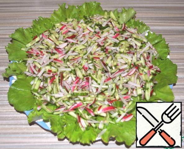 On the lettuce leaves, pour cucumbers and radishes.