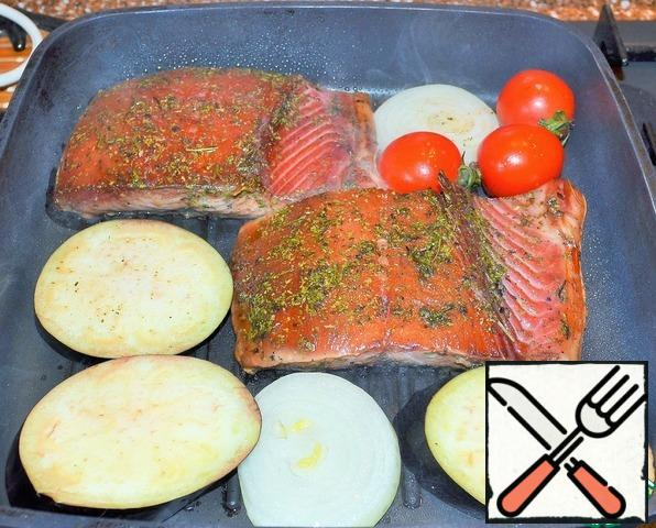 Preheat the grill pan over high heat. Grease the fish and vegetables with vegetable oil (it is convenient to do this with a brush) and put them in a frying pan. It is when using a grill pan that it is necessary to lubricate the products with oil, and not pour it into it.
