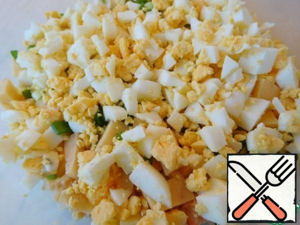 Crumble the eggs with a small cube. We open the boiled rice, send it to the salad and mix it quickly. You can lightly sprinkle everything with olive oil.