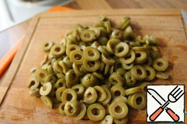 We drain the brine from the olives, cut them into rings.