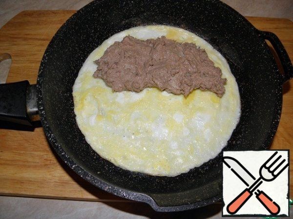 When the omelet thickens, put the liver mass on one half of it.