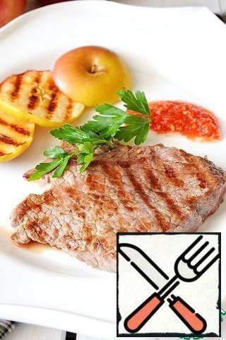 Serve the finished pork steak with grilled apples.