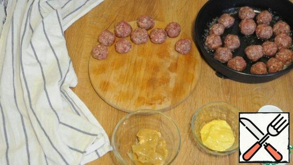 From the minced meat, we form small balls, fry in butter on all sides.