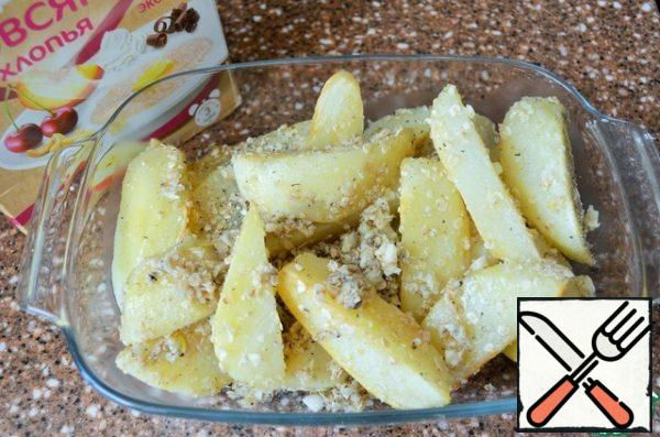 Put the potatoes in a heat-resistant form, season with flakes and garlic.