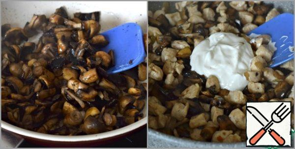 In parallel, in another pan, fry the randomly chopped mushrooms in vegetable oil (2 tbsp. l). Five minutes will be enough. Then put the mushrooms in a frying pan with chicken fillet and onion, add sour cream (50 g), mix. Add salt, season with your favorite spices (I use Adyghe salt).