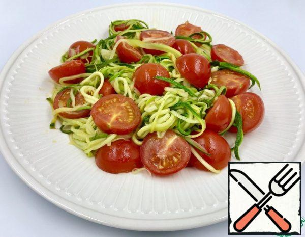 """Zucchini cut into """"noodles"""" using a grater for Korean carrots. The center of the zucchini with seeds is not used. Cut the garlic (plates) and cherry tomatoes (in half)."""