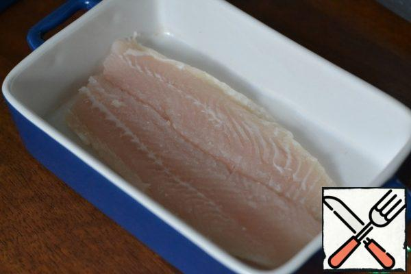 Grease the baking dish with sunflower oil. Wash and dry the fish. We put it in the form.