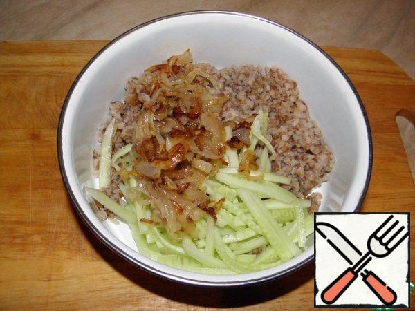 To the buckwheat porridge, add the fried onion, cucumber, mix, add salt and pepper to taste.
