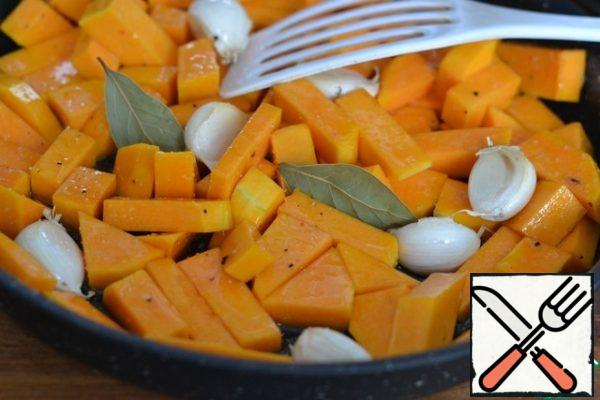 Put the pumpkin and garlic in a baking dish. Add 2 tablespoons of sunflower oil, salt and pepper. Add the bay leaf. Mix well. Bake in a preheated oven at 200g for 20 minutes.