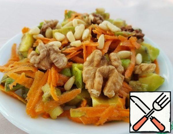 Grate the carrots on a coarse grater. Fry the crushed nuts in a pan and set aside. Cut the avocado pulp into identical pieces and put them in a bowl with orange juice.