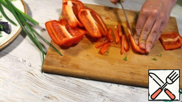 Sweet pepper is cleaned from the seeds, remove the partitions, cut into strips.