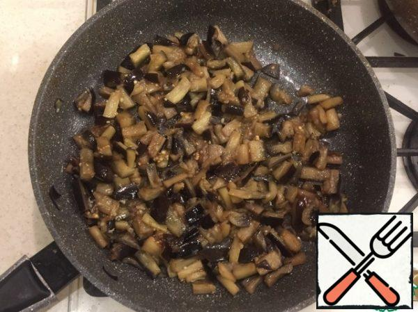 Finely chop the eggplants, cover with salt and leave for 20 minutes until moisture is released. Rinse well. Simmer in a frying pan until fully cooked. During cooking, add the garlic and a little salt (some salt has already been absorbed by the eggplant at the initial stage).
