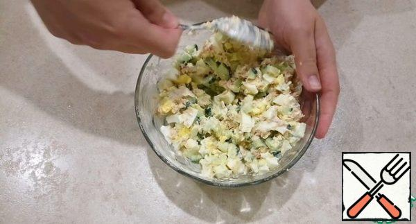 Mix the cucumber, eggs and tuna with mayonnaise. I'm salting a little, but it's not necessary to do this. Taste the salad and add salt if desired.