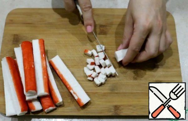 Let's cut the crab sticks into cubes.