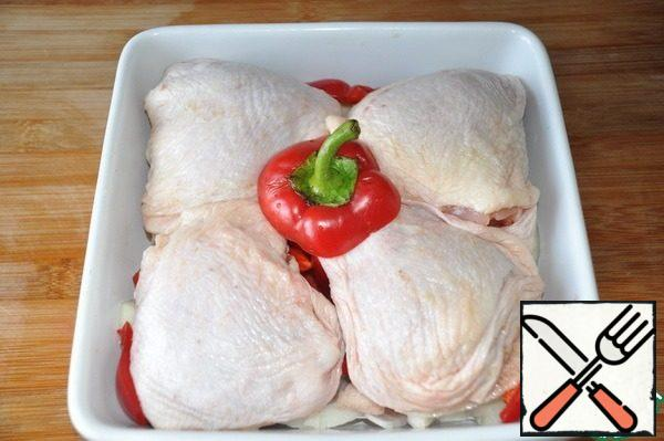 Chicken thighs are washed, dried. We take a convenient baking dish, put the onion and pepper down, on top of the thighs.