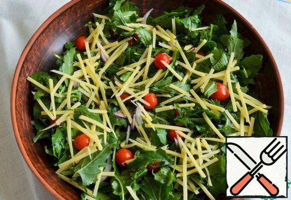 Add cherry and cheese straws to the greens.