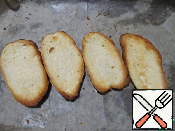 Sprinkle the baguette slices with olive oil and brown in a preheated 180 degree oven.