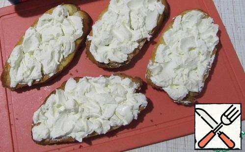 Cool the baguette slices and spread generously with cottage cheese.