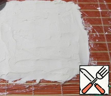 Spread the plastic wrap on a bamboo mat Put the cream cheese on the film, smooth it out until you get a rectangle.