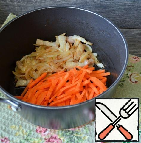 While the beets are stewing, heat 1 tbsp of vegetable oil in a deep saucepan, fry the pork belly with onion feathers, 5 minutes, medium heat. Add the carrot strips and fry for 5 minutes.