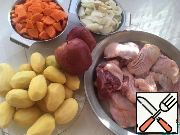 Prepare all the ingredients. I have already cut up the duck, onion feathers, carrots in half circles, garlic whole cloves, apples in quarters, removing the seeds.