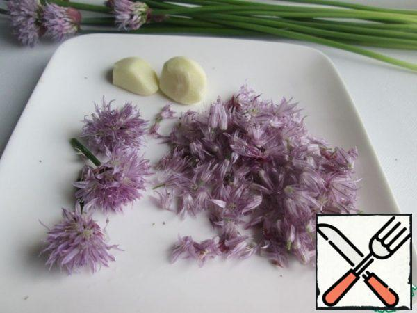 Wash the inflorescences, dry them and divide them into individual flowersFinely chop the tender feathers of the chives. Squeeze the garlic through a press.Add all prepared products to the soft butter. Add salt to taste. I added two pinches of salt. If desired, you can add sea salt and aromatic herbs.