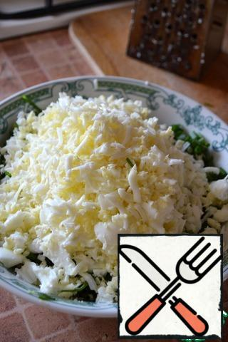 Grate the eggs and add them to the onion.