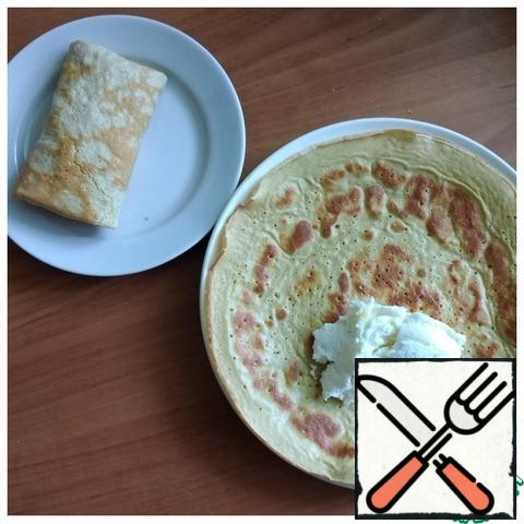 Since oatmeal pancakes are quite fragile for wrapping, we wrap the filling in them immediately, removing it from the pan. You can roll it up and then cut it into rolls. My filling: 1.8 % cottage cheese combined with honey.