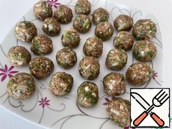 For the meatballs, chop the onion, garlic and herbs. From all the ingredients, knead the minced meat, add your favorite spices and salt to taste. We make meatballs the size of a quail egg. We send them to the refrigerator for 30 minutes.
