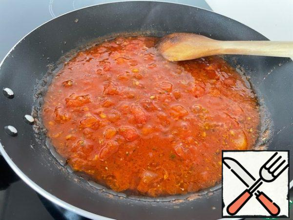 We prepare the sauce. Peel the tomatoes from the skin and cut into small cubes, lightly stew in oil, add tomato paste, spices and salt for an intense color. Depending on whether you like a lot of gravy in the dish, add water. It usually takes me 100 ml. Cook everything together for 5 minutes