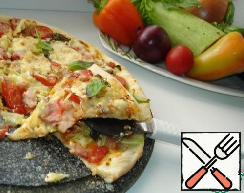 Pizza on a thin dough is obtained with a crispy crust from the bottom, a soft dough and a juicy filling.