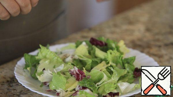 Starting the assembly. Attention - the number of ingredients is approximate!We spread the salad leaves on a plate