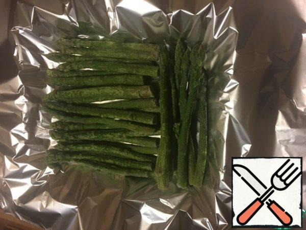 Spread the foil and put the asparagus on it, in general, asparagus can be replaced with any frozen vegetables (beans, broccoli, etc.)