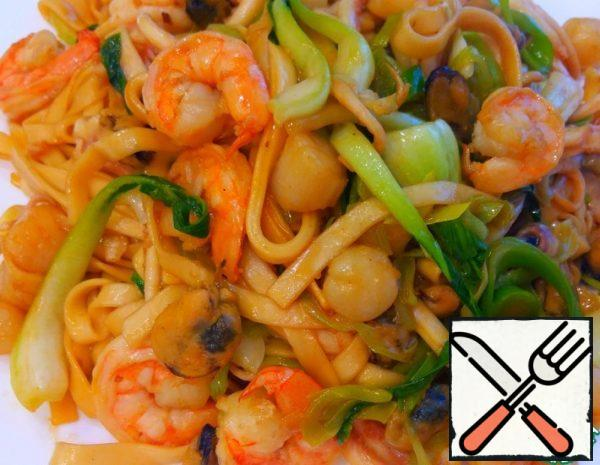 First, we boil the noodles, put them in a colander. We cut the cabbage and scald it. Then cut the leek into rings, finely chop the ginger, squid tentacles coarsely. We heat up the frying pan, pour the oil, put the ginger in the pan and immediately add the seafood there.