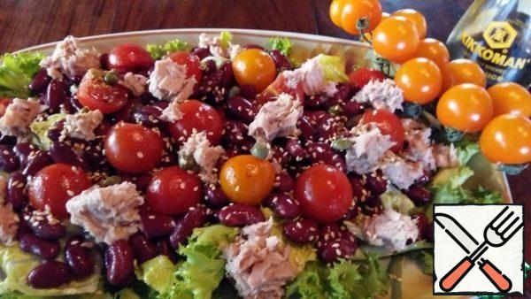 Put a layer of salad leaves on a dish, sprinkle with dressing. Place the beans with tomatoes and tuna slices on top, pour the dressing, sprinkle with capers and lightly fried sesame seeds.