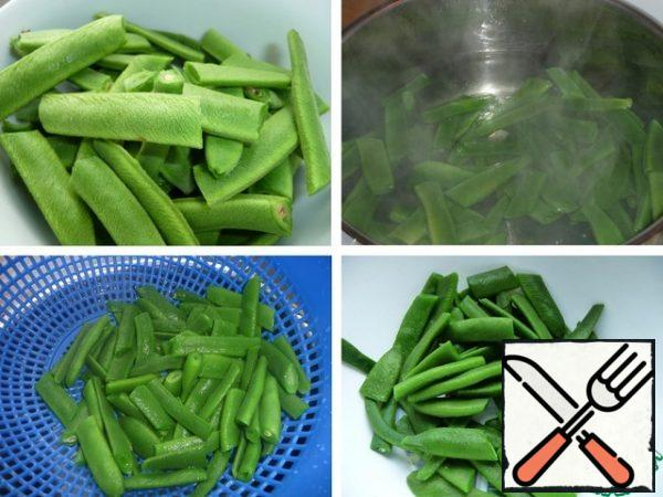 Wash the string beans, cut into several parts, boil in salted water until soft, about 5-7 minutes. Transfer to ice water for 4-5 minutes. Then discard the beans in a colander.