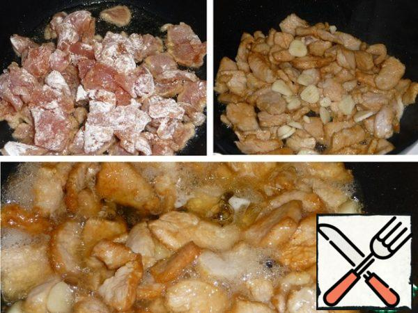 In a cauldron or deep frying pan, heat the vegetable oil, lower the meat into boiling oil, lightly fry, add garlic, fry briefly, pour in white wine. Evaporate completely.