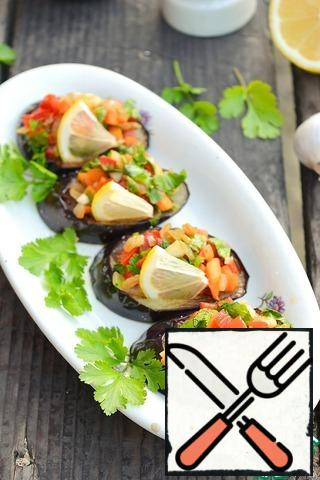 """Put the vegetable mixture on the eggplant slices, decorate the snack with a slice of lemon. Vegetables can be warm or completely cooled. Delicious in any case.This snack is convenient to take with you to nature. Place the fried eggplant slices in one container, and the vegetable filling in the other. Collect a snack in nature.It is very convenient to prepare a snack in advance. Prepare the vegetable filling and fry the eggplant. Also put them in containers and put them in the refrigerator, and at the right time collect a snack. Vegetables and eggplants in the """"disassembled"""" form are stored in the refrigerator for up to 3 days."""