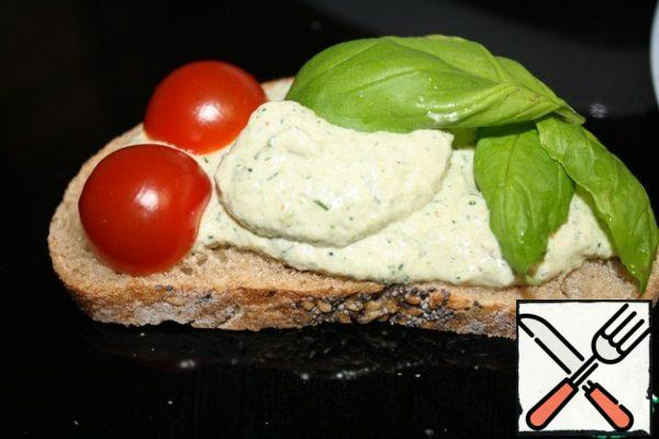 Very tasty pate on a piece of bread with herbs and vegetables.