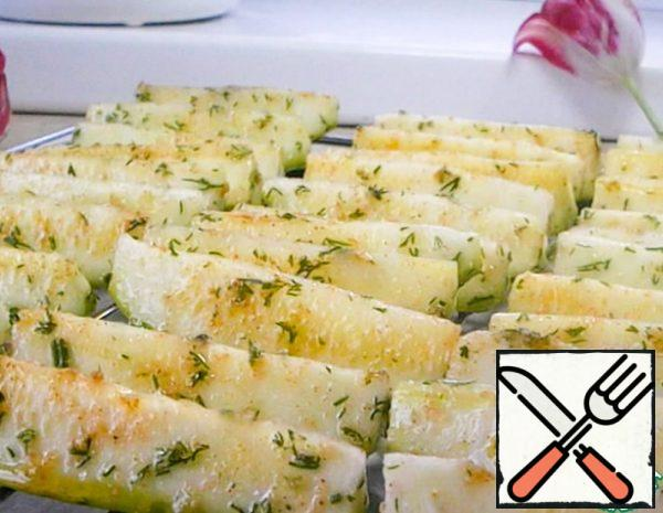 We cut young zucchini into cubes about 5 cm long. We cut a small zucchini lengthwise into 6-8 parts as shown in the video. Pour 1 tablespoon of vegetable oil and mix well so that it evenly covers the cubes. Sprinkle the zucchini with salt, paprika, dry ground garlic (fresh is not suitable) and add a little chopped herbs. Mix again and put it on a baking sheet or an oven grill.