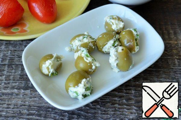 Stuff the olives with cottage cheese mass.