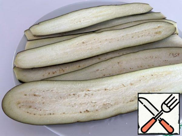 We use elongated eggplants. Cut into thin plates along the entire length, salt and leave for 5 minutes.