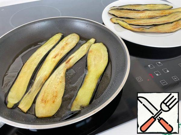 Heat the oil in a frying pan and fry the eggplants on both sides.
