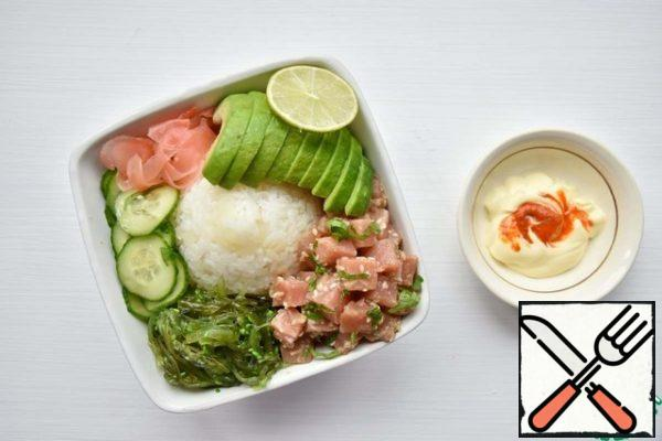 Place a pile of rice in the center of the plate. Place additional ingredients closer to the edges of the plate: cucumber slices (radish), pickled ginger, avocado, chuka seaweed, fish. Mix the mayonnaise with the sriracha sauce and add it over the rice. Sprinkle the dish with sesame seeds.