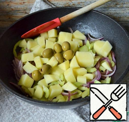 Add the potato cubes and olives, fry for 5 minutes, stirring.