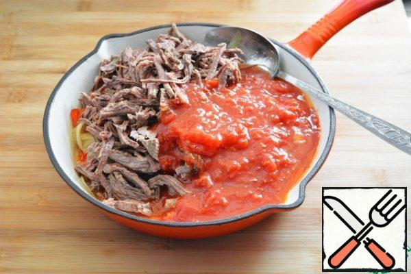 When the peppers and onions are slightly fried, add the beef disassembled into fibers and mashed tomatoes in their own juice to the pan and pour in the broth. Simmer all together for about 2-3 minutes