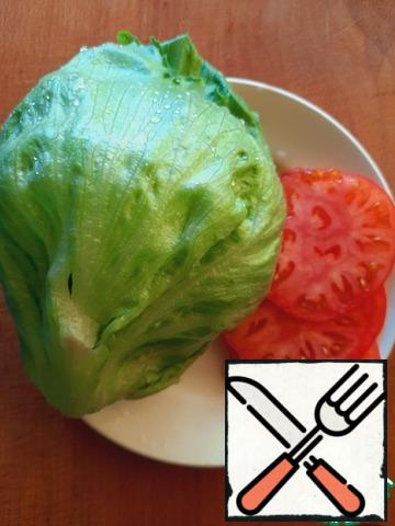 Prepare other ingredients for the sandwich: cut the tomato into thin rings, and the cheese into plates, prepare a couple of iceberg lettuce leaves.