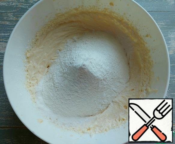 Next, sift half a portion of flour and baking powder of the dough. Beat it up.
