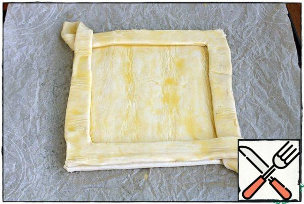 We do the same with the other side and transfer it to the vacant part of the square. We trim the sides, press them slightly so that they are glued to the square and also lubricate the egg on top, send it to the preheated oven for 10-15 minutes.